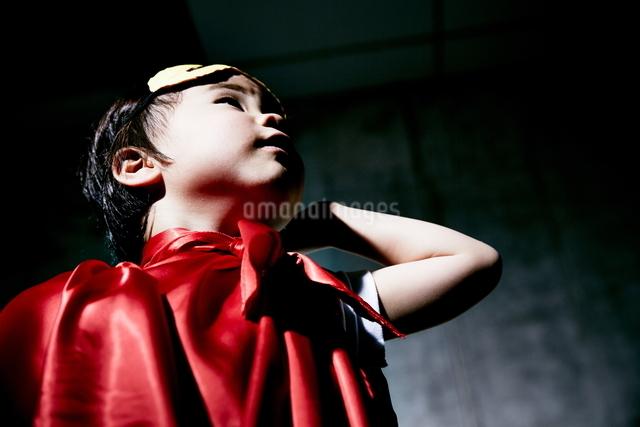 コンクリートの壁の前でポーズをキメるヒーローの男の子のアップの写真素材 [FYI01638475]