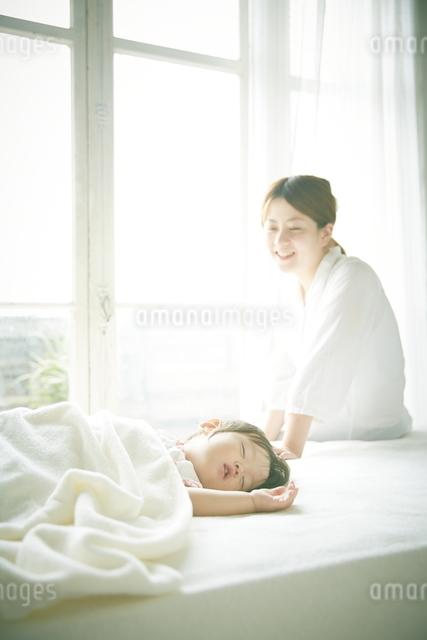 ベッドの上でお昼寝する赤ちゃんをお母さんが優しく見つめているの写真素材 [FYI01638492]