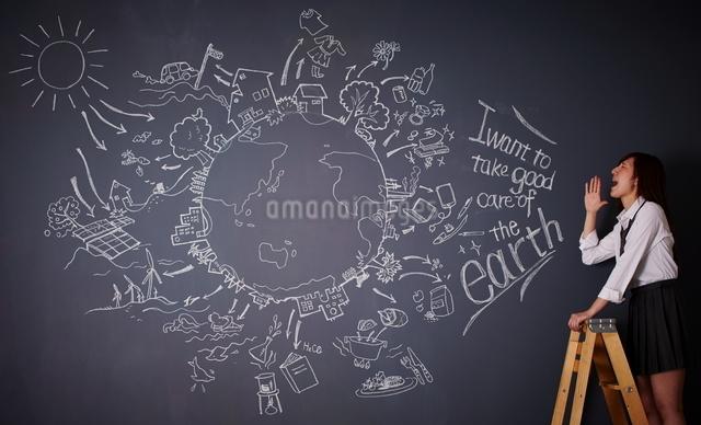黒板に描かれた地球の絵に向かって叫ぶ女性のイラスト素材 [FYI01638496]