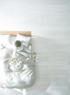 白い床の寝室にあるベットで起床した女性の写真素材 [FYI01638506]