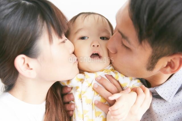 赤ちゃんにキスする両親の写真素材 [FYI01638570]
