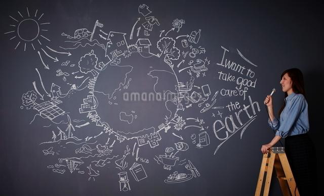黒板に描かれた地球の絵に向かってマイクを持つ女性のイラスト素材 [FYI01638578]