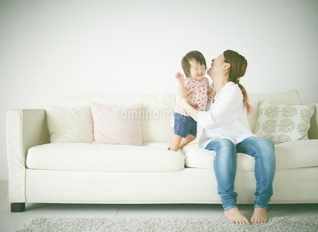 ソファーの上で遊んでいる親子の写真素材 [FYI01638594]