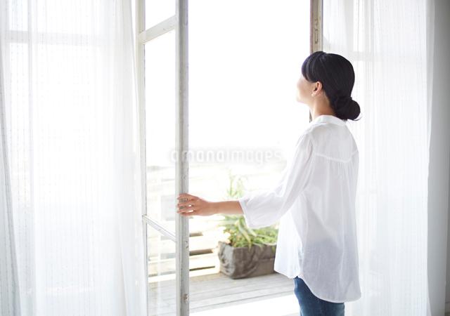 窓を開ける女性の写真素材 [FYI01638602]