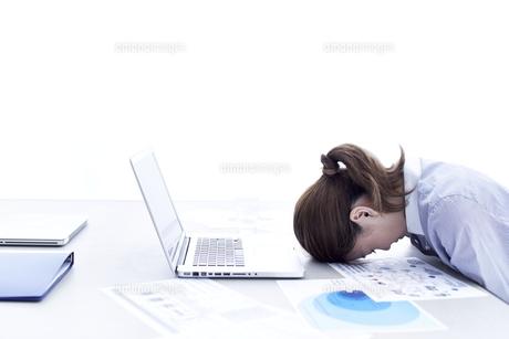 パソコンの前でうつむく女性の写真素材 [FYI01638634]