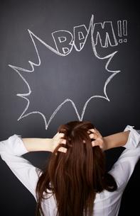 黒板に描かれた吹き出しの前で頭を抱える女性のイラスト素材 [FYI01638640]