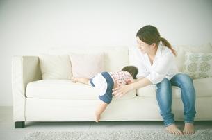 ソファーによじ登る赤ちゃんを微笑ましく支えるお母さんの写真素材 [FYI01638666]