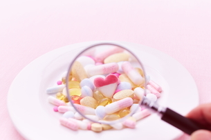お皿に乗ったサプリメントを虫眼鏡で見る女性の写真素材 [FYI01638671]