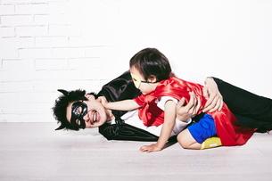悪者をやっつけているヒーローの男の子の写真素材 [FYI01638756]