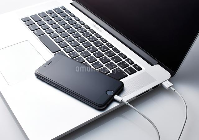 パソコンに繋がっているスマートフォンの写真素材 [FYI01638780]