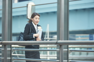 書類を持って急いでいる働く女性の写真素材 [FYI01638785]