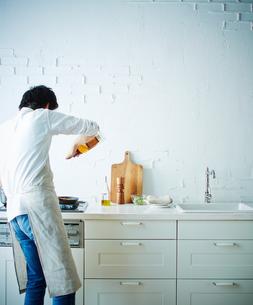 キッチンで料理をする男性の後姿の写真素材 [FYI01638838]