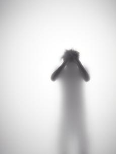 頭を抱えている男性のシルエットの写真素材 [FYI01638839]