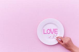 お皿に乗った愛のサプリメントを手に取る女性の写真素材 [FYI01638854]
