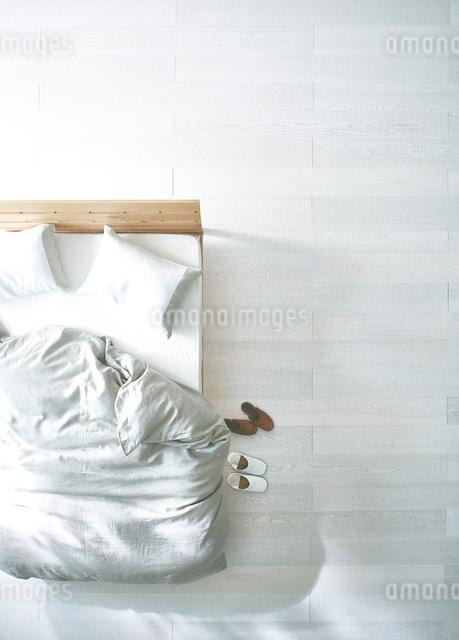 白い床の寝室にあるベットと二足のスリッパの写真素材 [FYI01638862]
