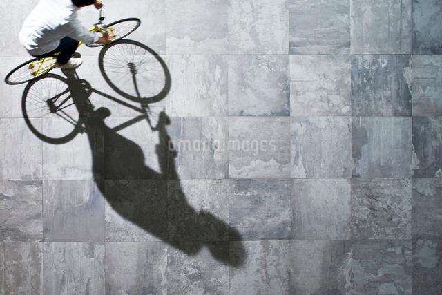 光が差し込む石の床を自転車で走る男性の写真素材 [FYI01638869]
