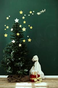 黒板風の壁の前にあるクリスマスツリーの写真素材 [FYI01638872]
