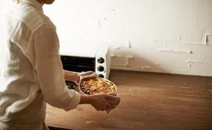 オーブンから焼いたパイを取り出す女性の写真素材 [FYI01638879]