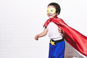 レンガの壁の前で走っているヒーローの男の子の写真素材 [FYI01638885]