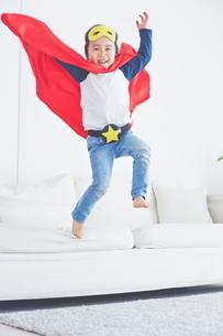 ソファーからジャンプするちびっこスーパーマンの写真素材 [FYI01638920]