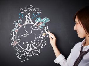 黒板に地球の絵を描く女性のイラスト素材 [FYI01638926]