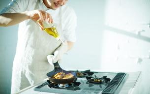 キッチンで料理する男性の写真素材 [FYI01638958]