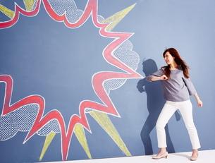 黒板に書かれた吹き出しの横でポーズをとっている女性のイラスト素材 [FYI01638959]