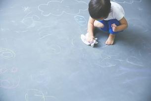 大きな黒板の落書きを消している男の子のアップの写真素材 [FYI01639050]