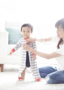 母親に着替えをさせてもらっている子供の写真素材 [FYI01639070]