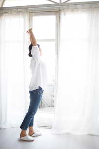窓際でストレッチしている女性の写真素材 [FYI01639153]