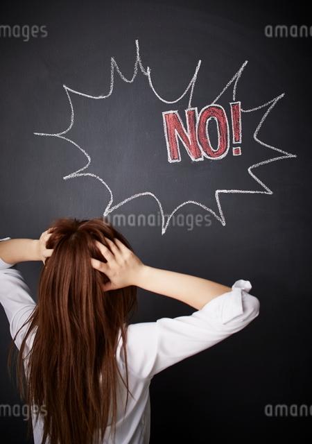 黒板に描かれた吹き出しの前で頭をかかえる女性のイラスト素材 [FYI01639165]