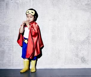 コンクリートの壁の前でポーズをキメるヒーローの男の子の写真素材 [FYI01639175]