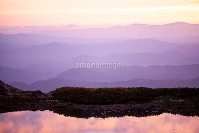 夕日で赤く染まる御嶽山五の池と山並みの写真素材 [FYI01639651]