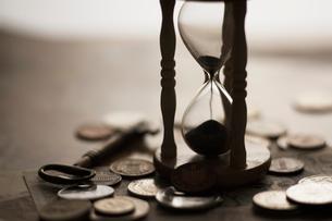 昔の外国のお金と砂時計の写真素材 [FYI01642042]