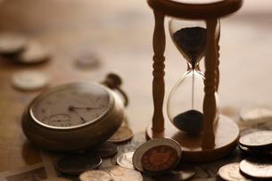 昔の外国のお金と砂時計の写真素材 [FYI01642522]