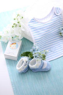 水色の机のブルーのベビーグッズとお花の写真素材 [FYI01643212]