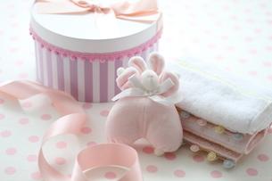 水玉の机のピンクのベビーグッズとピンクストライプのボックスの写真素材 [FYI01643226]