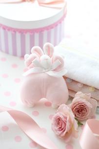 水玉の机のピンクのベビーグッズとピンクストライプの箱とバラの写真素材 [FYI01643232]