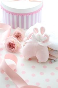水玉の机のピンクのベビーグッズとピンクストライプの箱とバラの写真素材 [FYI01643251]