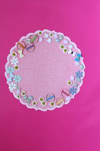 濃いピンクの背景と丸い紙の縁にパーツと花の写真素材 [FYI01643269]