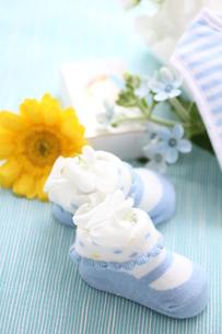 水色の机のブルーのベビーシューズにお花のアレンジの写真素材 [FYI01643335]
