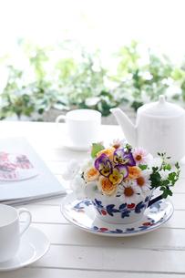 ティータイム、テーブルの上の花のアレンジとティーポットとカップ&ソーサー(生花)の写真素材 [FYI01643342]
