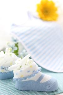 水色の机のブルーのベビーシューズにお花のアレンジの写真素材 [FYI01643366]