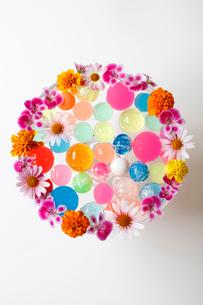 まわりに花を活けたガラスの器に入ったカラフルなボール(生花)の写真素材 [FYI01643400]
