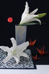 青い器に活けた白い百合と赤いかんざしと赤と金の市松模様の折鶴(生花)の写真素材 [FYI01643402]
