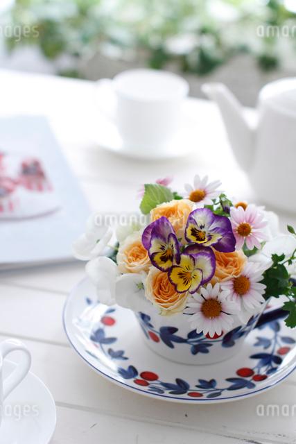 ティータイム、テーブルの上の花のアレンジとティーポットとカップ&ソーサー(生花)の写真素材 [FYI01643413]