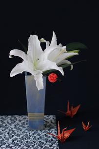青い器に活けた白い百合と赤いかんざしと赤と金の市松模様の折鶴(生花)の写真素材 [FYI01643425]