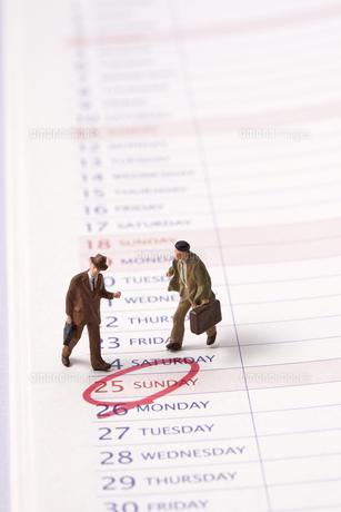 ビジネスマンのミニチュア人形とスケジュール帳の写真素材 [FYI01644104]