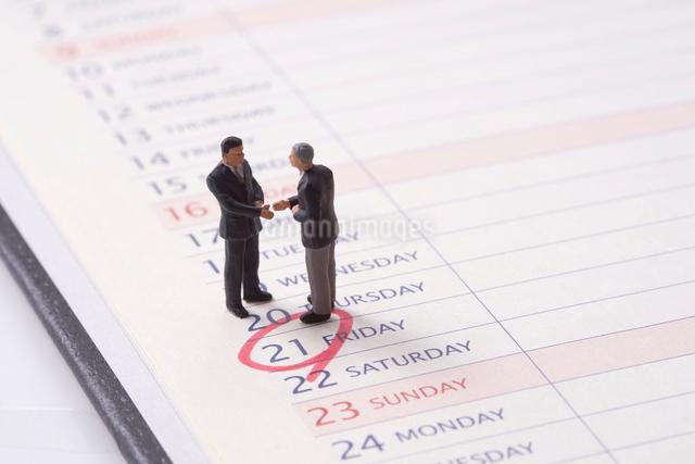 ビジネスマンのミニチュア人形とスケジュール帳の写真素材 [FYI01645130]