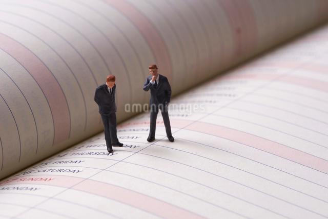ビジネスマンのミニチュア人形とスケジュール帳の写真素材 [FYI01645372]